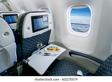 Commercial passengers airplane interior of seat chairs, window and tray with food