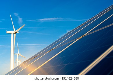 Commercial solar panel with large wind turbines behind on a clear day