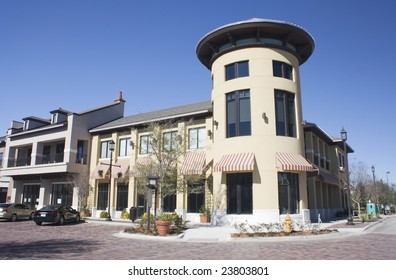 commercial strip mall with circular corner tower and striped awnings