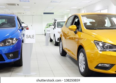 Commercially colourful shining cars stand in light car shop.