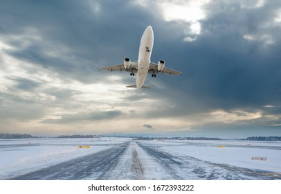 Commercical white airplane fly up over take-off runway the (ice) snow-covered airport- Norway