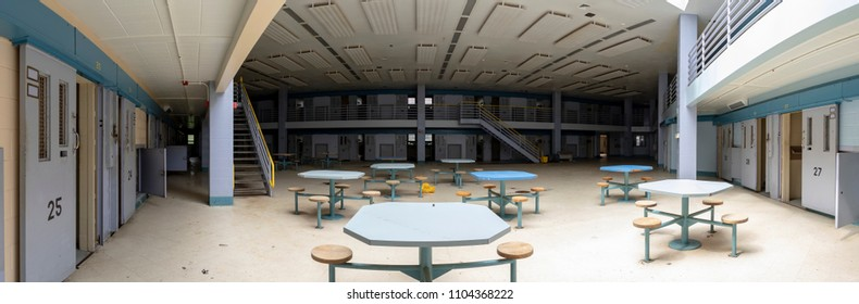 Common area inside abandoned prison cellblocks with open doors.