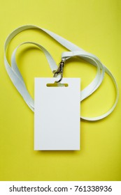 A common blank label name tag hanging on the neck with a red thread. Empty layout isolated on yellow.
