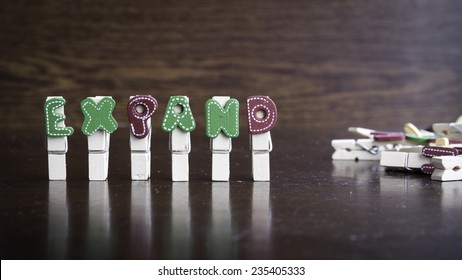 Common business terms - Slightly defocused and close-up of EXPAND word on clothes peg stick with lots of clothes peg at background
