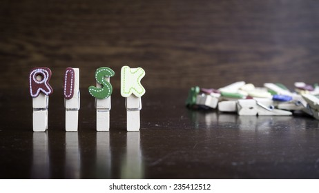 Common business terms - Slightly defocused and close-up of RISK word on clothes peg stick with lots of clothes peg at background