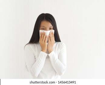 common cold and flu or influenza epstein barr virus or EBV and sinusitis, nasal polyp and asthma in woman and she hold white paper napkin close on nose on white background use for health care concept.