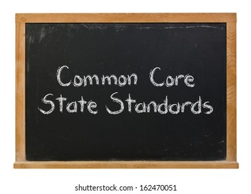 Common Core State Standards written in white chalk on a black chalkboard isolated on white