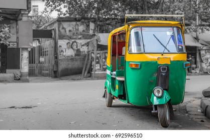 Common Indian auto rickshaw on a city street at Kolkata with bokeh retro background.