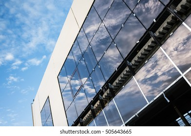 Common industrial architecture example. Facade of modern building under construction, wall of shining glass
