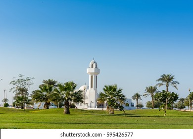 A common stone mosque with green meadow and trees in the Corniche park in the city of Dammam, Kingdom Saudi Arabia