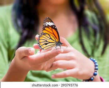01be0b392 Common Tiger butterfly hanging on girl's finger, outdoor in nature