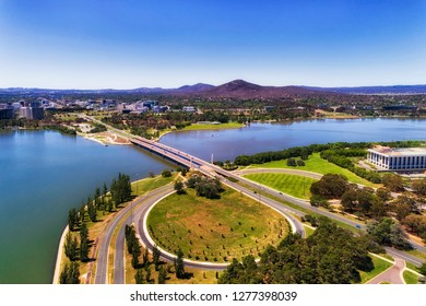 Commonwealth avenue and bridge over Burley Griffin lake in Canberra between city CBD and federal government capital hill triangle area with local streets, roads, parks and buildings.