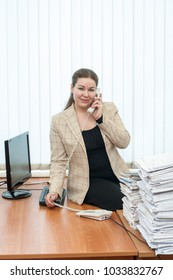 Communicable positive office assistant standing at desk and calling by telephone