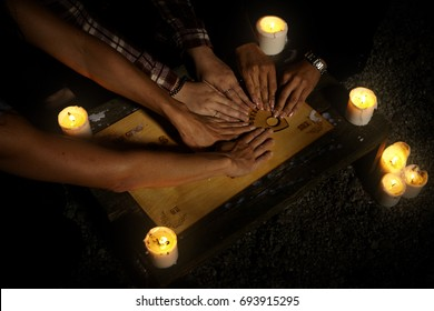 Communicating with ghosts through spiritual board under candle lights