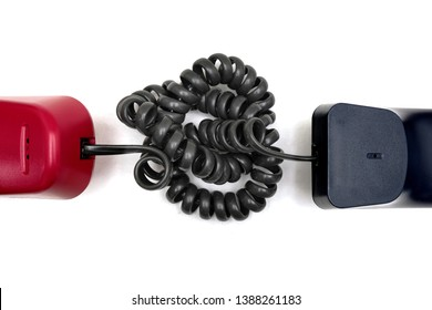 Communication barrier - a tangled coil cord with a pair of telephone handset, connected but not getting through, concept for communication breakdown, misunderstanding or lost in translation.
