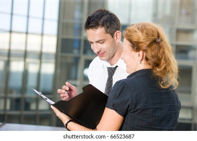 Communication between office workers man and woman about signing documents. Red-haired lady showing papers to her boss from foreign partners to be signed.