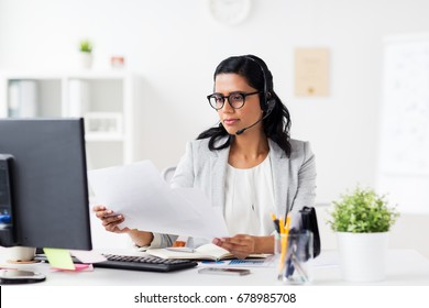 communication, business, people and technology concept - businesswoman or helpline operator with headset, computer and papers at office