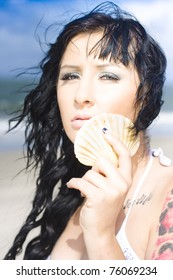 Communication Concept With A Beautiful Brunette Girl Listening To The Ocean Sound Through A Seashell Or Sea Shell In An Outdoor Glamour Portrait