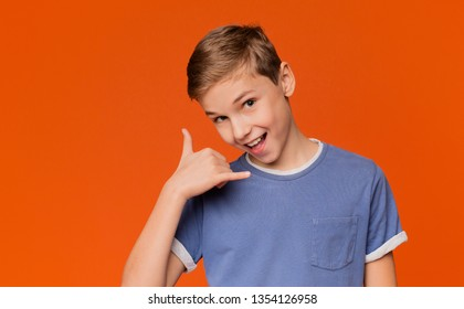 Communication concept. Flirty boy making call me gesture, smiling at camera, orange background with free space