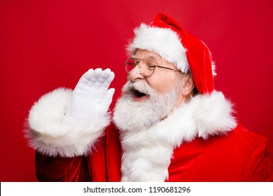 Communication concept. Profile side view photo of excited funny kind stylish Santa Claus with open mouth hold palm hand near face saying loud ho-ho-ho isolated on vivid red background