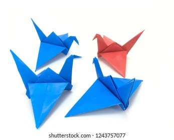 Communication concept. Red origami bird communicates with blue origami birds. Leadership concept. Red origami bird leads the group. Copy Space.