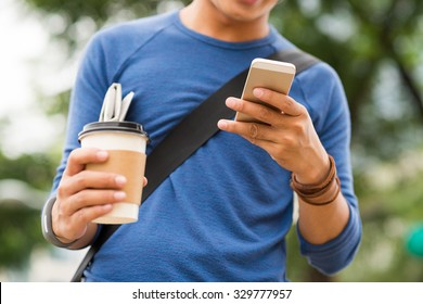 Communication concept: young man checking his phone when going to work