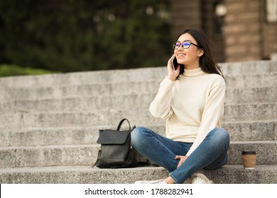 Communication And Education Concept. Cheerful asian teen in specs making phone call, sitting on steps, outdoor