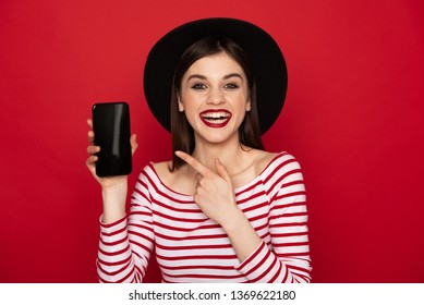 Communication every moment. Waist up portrait of happy laughing brunette lady pointing at screen of mobile phone. Isolated on red