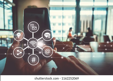 Communication fintech sign icon and connection screen of smartphone with blur cafe coffee shop background. Financial business technology freedom dream life using internet freedom life concept.