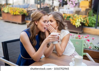 communication and friendship concept - smiling young women drinking coffee and gossiping at street cafe