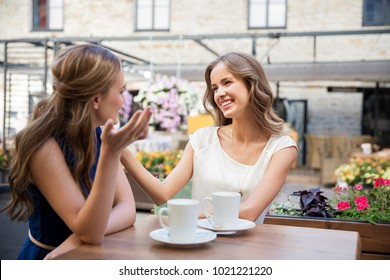 communication, friendship and people concept - happy young women drinking coffee at outdoor cafe