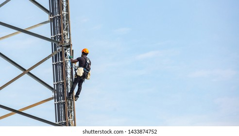Communication maintenance. Technician climbing on telecom tower antenna against blue sky background, copy space.