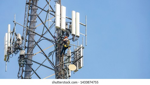 Communication maintenance works. Technician climbing on telecom tower antenna against blue sky background, copy space.