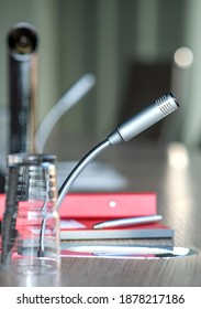 Communication, media or news concept: close-up of a isolated microphone in an office with notekook and pencel- selective focus, lots of copyspace, portrait format