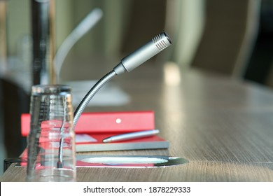 Communication, media or news concept: close-up of a isolated microphone in an office with notekook and pencel- selective focus, lots of copyspace, blurred background