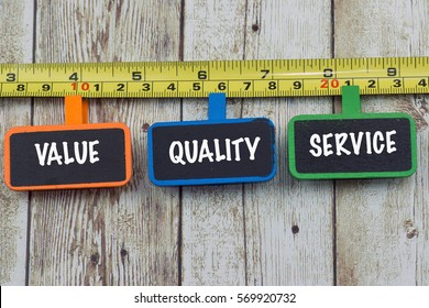 Communication message motivation concept with VALUE QUALITY SERVICES word on wooden tag and measure tap on wooden table
