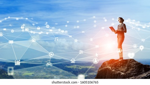 Communication network concept. Young businesswoman on the mountain top.