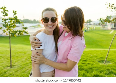 Communication of the parent and adolescent, mother hugging daughter. Background green lawn, recreation and entertainment zone
