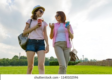 Communication of parent and teenager. Mother is talking to her teen daughter for 14 years, walking around the park on sunny summer day. Nature, sky in clouds background