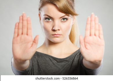 Communication psychology negative defensive concept. Assertive woman making stop gesture. Strong blonde lady showing hold sign.