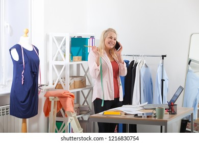 Communication with suppliers by phone, skype. Beautiful woman tailor talking on  phone, standing near table in workshop with clothes.