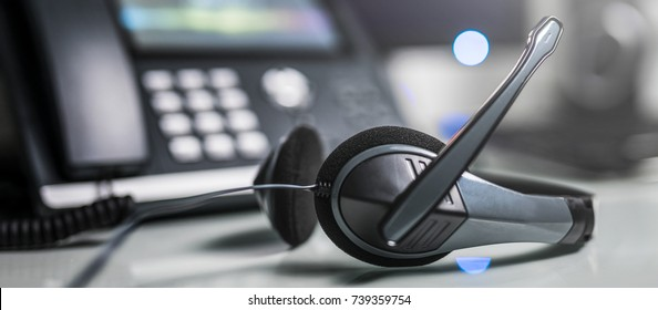 Communication support, call center and customer service help desk. VOIP headset on laptop computer keyboard.