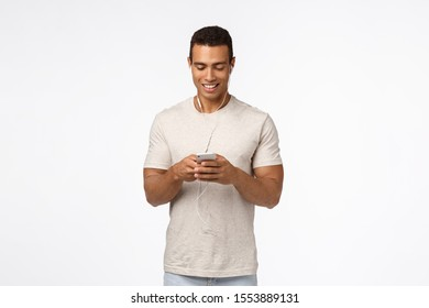Communication, technology and mobile device concept. Handsome athletic man in casual outfit, wear earphones, hold smartphone and smiling looking mobile screen, message friend, watch video in subway