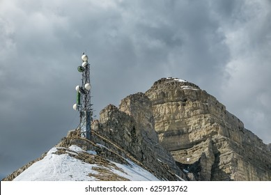Communication tower on snowy mountain against stormy sky background in difficult alpine terrain