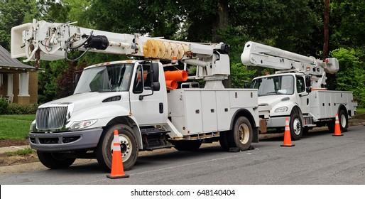 Communication utility trucks parked in residential neighborhood. Horizontal.