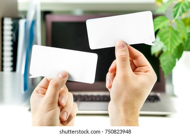 Communication at work, business interaction, learning new foreign language in school or debate concept. Hands holding two blank speech bubbles in front of a laptop in office workstation.