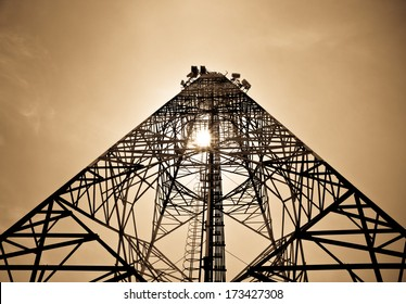 communications tower with antennas against sky background