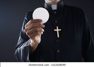 Communion wafer hostia priest in hands with cross