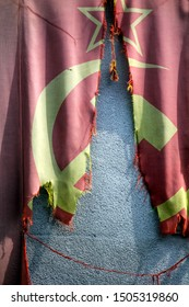 communist flag torn in half in front of a wall in Berlin in Germany