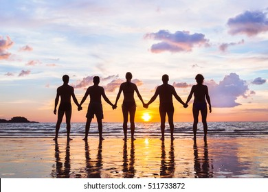 community or group concept, silhouettes of people holding hands and standing together, team on the beach, unity background